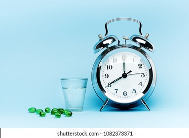 Medical green capsule pills, glass water and alarm clock on blue background. Concept health