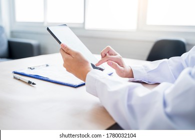 Medical healthcare clinic Asian hand using smart tablet device technology diagnosing patient symptoms health and research records doctor working at home modern office using wireless online technology