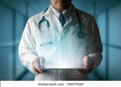 Medical Healthcare Concept - Doctor in hospital looking at tablet computer.
