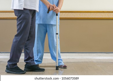 Medical and healthcare concept, Physiotherapist in blue attire to take care of the elderly in the clinic, walking stick helps the elderly to walk better. with copy space for text