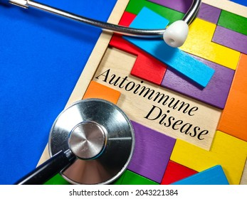 Medical and healthcare concept.Text Autoimmune Disease wiriting on colored wooden puzzle with clock and stethoscope on blue background.