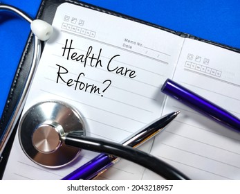 Medical and healthcare concept.Text Health Care Reform? wiriting on notebook with pen and stethoscope on blue background.