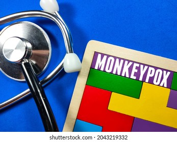 Medical and healthcare concept.Text MONKEYPOX wiriting on colored wooden puzzle with stethoscope on blue background.