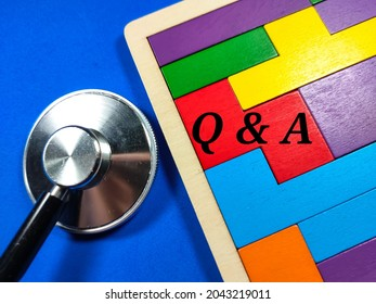 Medical and healthcare concept.Text Q AND A wiriting on colored wooden puzzle with stethoscope on blue background.
