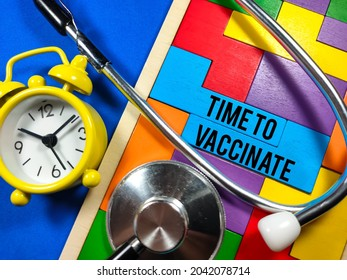 Medical and healthcare concept.Text TIME TO VACCINATE wiriting on colored wooden puzzle with clock and stethoscope on blue background.