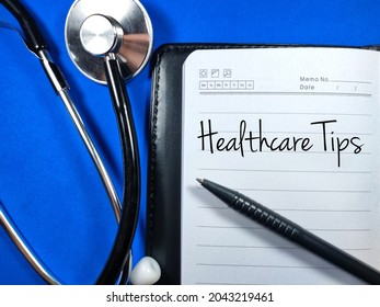 Medical and healthcare concept.Text Healthcare Tips wiriting on notebook with pen and stethoscope on blue background.