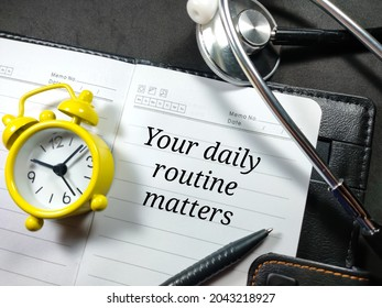 Medical and healthcare concept.Text Your daily routine matters wiriting on notebook with alarm clock,pen and stethoscope on black background.
