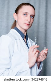 Medical healthcare. Doctor with syringe, injection in hospital.  Professional medicine health clinic practitioner. Adult person. People in white uniform, coat in lab. Happy confident female.