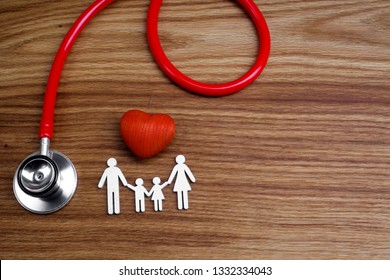 Medical Insurance Concept. Family cutout and Stethoscope on wooden background