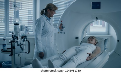 In Medical Laboratory Female Radiologist Controls MRI or CT or PET Scan with Female Patient Undergoing Procedure. Doctor Conducts Emergency Scanning with Advanced Medical Technologies. In Blue Tone.