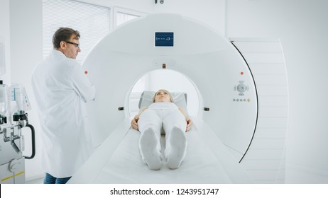 In Medical Laboratory Male Radiologist Controls MRI or CT or PET Scan with Female Patient Undergoing Procedure. Doctor Conducts Emergency Scanning with Advanced Medical Technologies.