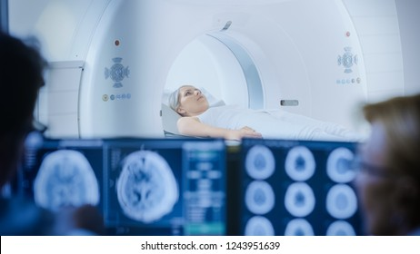 In Medical Laboratory Patient Undergoes MRI or CT Scan Process under Supervision of Doctor and Radiologist in Control Room, They Watche Procedure and Monitors Brain Activity Results.