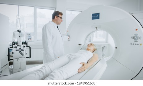 In Medical Laboratory Radiologist Controls MRI or CT or PET Scan with Female Patient Undergoing Procedure. Professional Doctor Conducts Emergency Checkup Procedure with Advanced Medical Technologies.