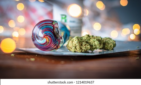 Medical marijuana with blown glass pipe and bokeh lights