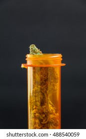 Medical Marijuana Bud Prescription Cannabis In Bottle Close Up On Black Background. Selective Focus With Copy Space.