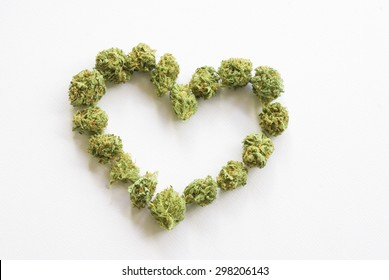 Medical marijuana buds arranged into a heart shape against a white background