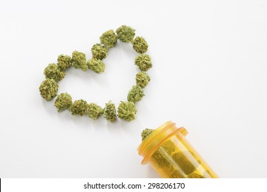 Medical marijuana buds arranged into a heart shape near an orange prescription pill bottle