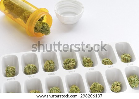 Medical marijuana buds arranged in a prescription pill bottle and a weekly pill box