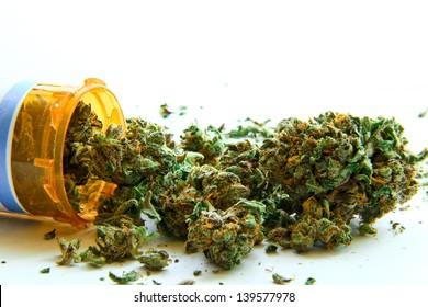 Medical Marijuana C. Medical marijuana pouring out of a prescription bottle against white.