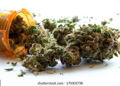 Medical Marijuana D. Medical marijuana pouring out of a prescription bottle against white.