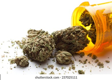 Medical Marijuana pouring out of a prescription bottle against white