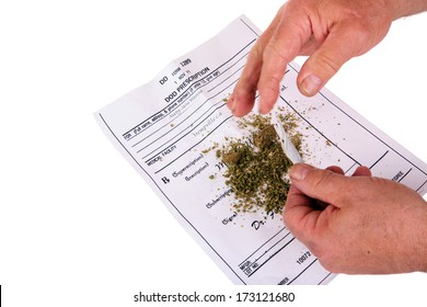 A medical Marijuana user rolls a Joint with rolling papers over his Medical Marijuana certificate in order to smoke some pot and relieve all his pain and suffering from ills real and imaginary