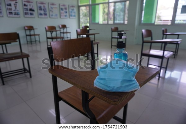 Medical mask and alcohol hand wash gel on the wood lecture chairs in the empty classroom. Concept during the Coronavirus Disease COVID-19 outbreak and pandemic in the 2020s. Back to school concept.