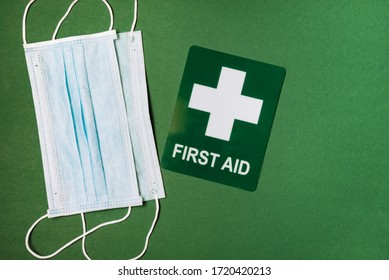 Medical mask and first aid sign on green background