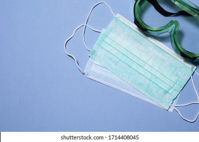 medical masks and doctor's special glasses on a blue background. Copy space
