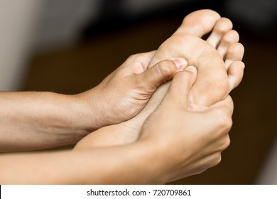 Medical massage at the foot in a physiotherapy center. Female physiotherapist inspecting her patient.