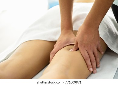 Medical massage at the leg in a physiotherapy center. Female physiotherapist inspecting her patient.