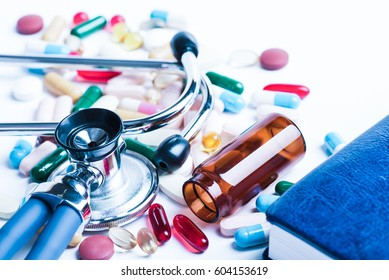 Medical, medicine stethoscope and pills on the notebook or notepad on blue background. Health care or illness. Tablet or drug in hospital or pharmacy. Cardiology heart treatment