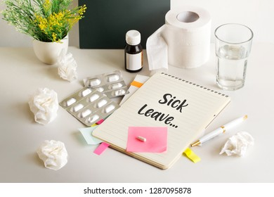 "Medical objects on office table top with text on memo pad ""Medical Leave""."