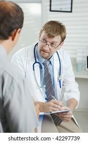 Medical office - Patient telling H1N1 flu symptoms to listening doctor.