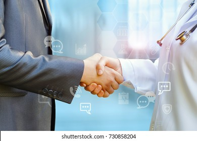 Medical officer and shaking hands with businessman on blurred background.