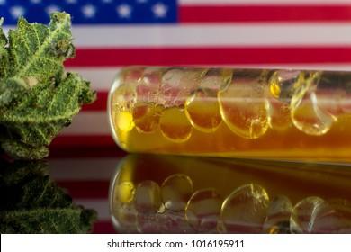 Medical Oil Cannabis - flower marijuana and oil cannabis with USA flag on the mirror background.