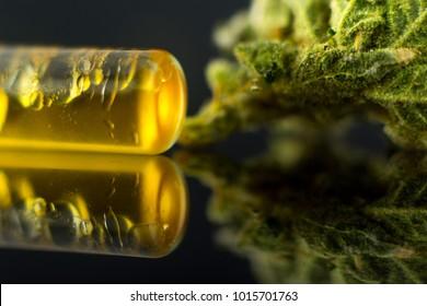Medical Oil Cannabis - marijuana flower and oil cannabis on the mirror black background.