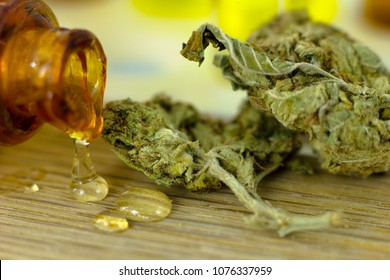 Medical Oil Cannabis - marijuana flower, oil cannabis on fresh oak piece of wood and oil test tubes with rack on the white background.