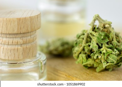 Medical Oil Cannabis - marijuana flowers on the wooden stopper with cannabis oil in small glass bottle.