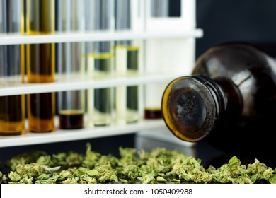 Medical Oil of Cannabis - oil test tubes with rack and antique old apothecary brown jar with marijuana on the black mirror background.