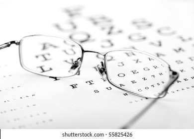 Medical optics concept with glasses on eye chart - monochrome