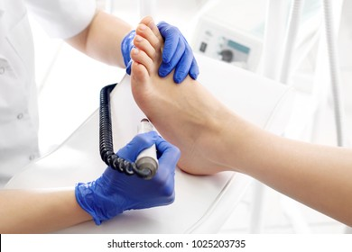 Medical pedicure. Podologist develops feet with a milling machine.