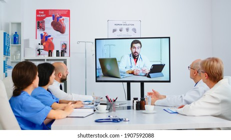 Medical people carefully listening online video presentation in boardroom office using modern technology. Doctors having conference with specialist medic and taking notes on clipboard using videocall.