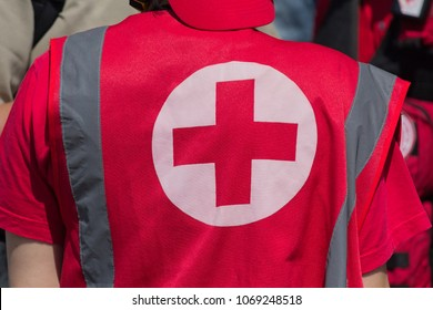 Medical personnel in uniform with the sign of the Red Cross provide medical assistance at a mass event