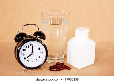 Medical pill and water with alarm clock on wood table in the time for healthy