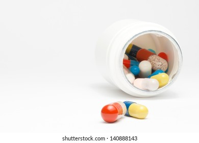 medical pills in laboratory near white container on white table with space for text