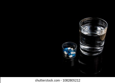 Medical pills next to a glass of water isolated  on a black background