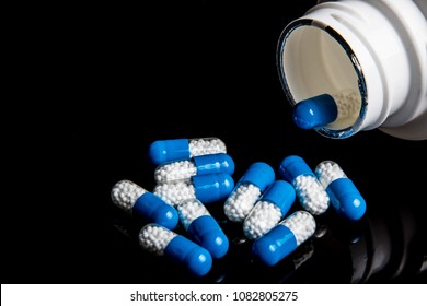 Medical pills spilling from a bottle on a black background