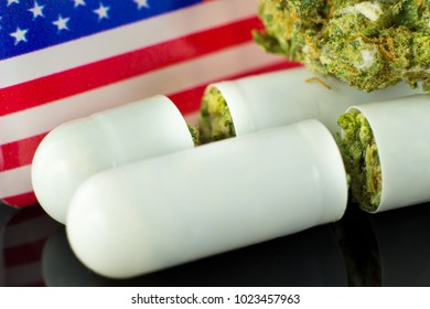 Medical Pills and tablets of Cannabis - marijuana flowers in white  capsules with USA flag on the black mirror background.