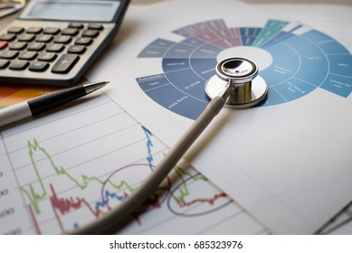 Medical practice financial analysis charts with stethoscope and calculator concept
